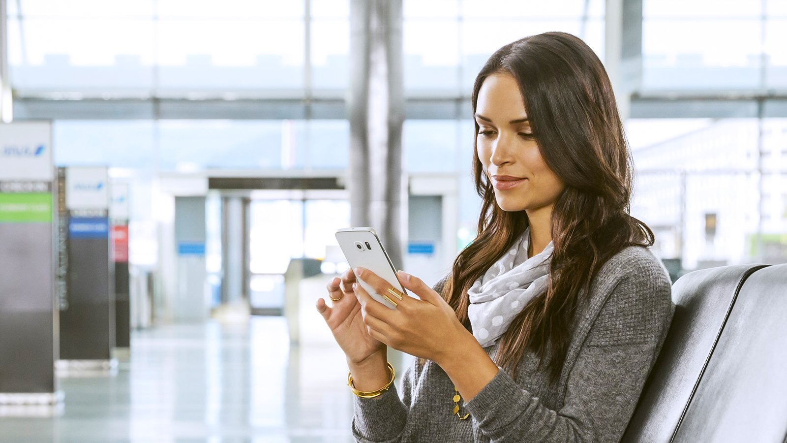 Woman in airport using mobile phone.
